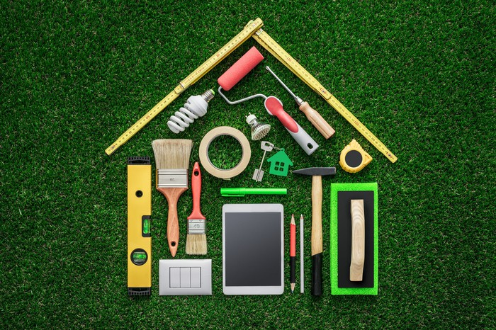 An assortment of hand tools laid against green background in the shape of a house.
