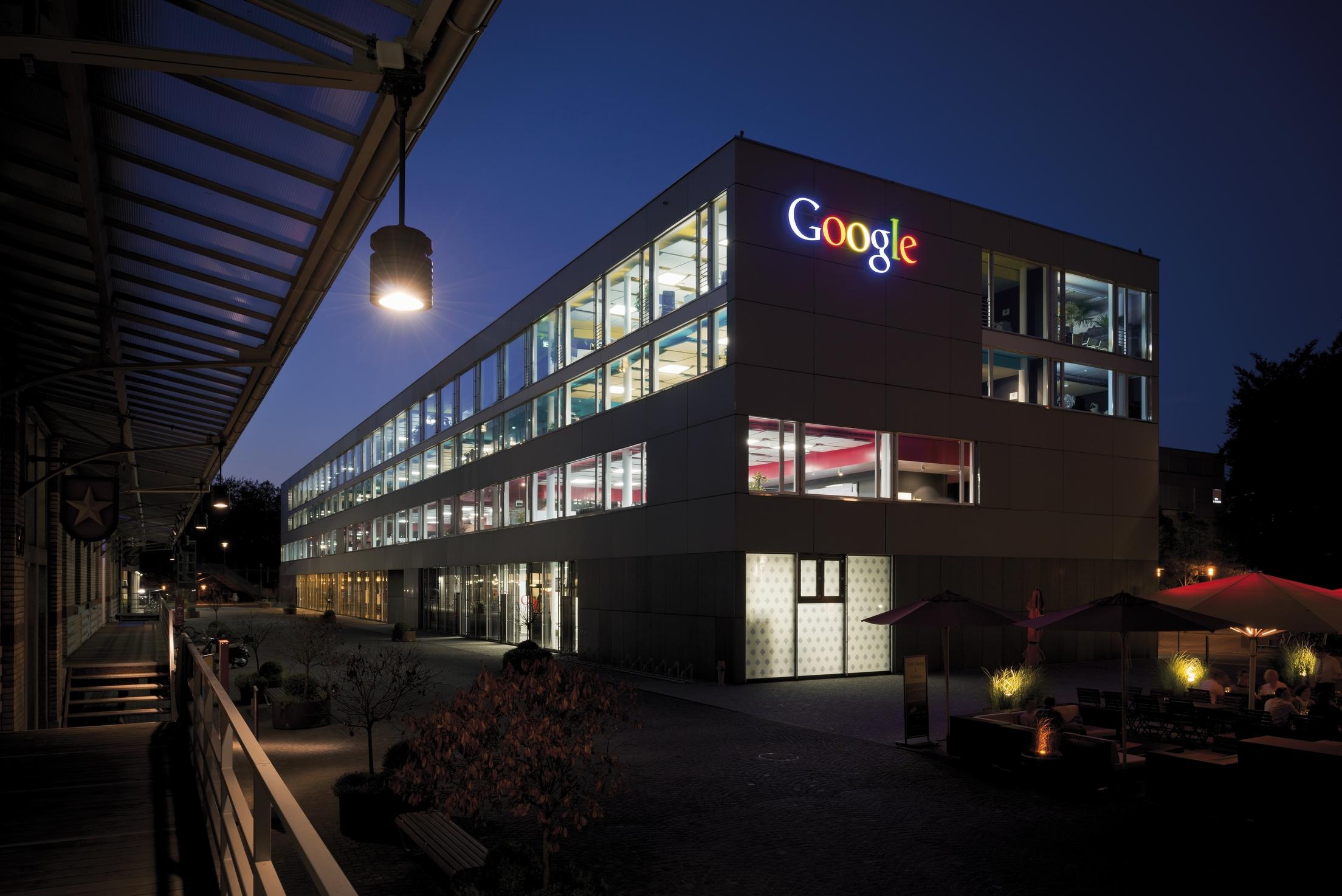 Building with the Google logo illuminated at night.