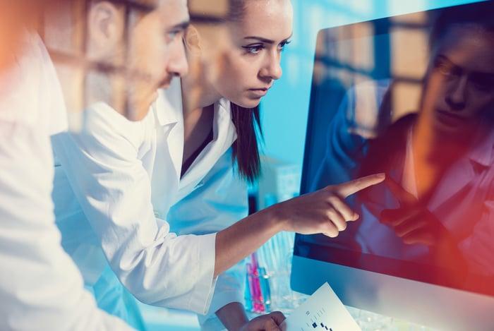 Man and woman wearing lab coats looking at a monitor