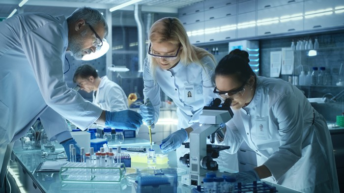 Scientists working with a microscope and a pipette in a lab.