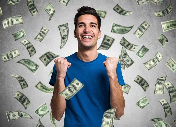 hundred-dollar bills rain down on a young man wearing a blue shirt.