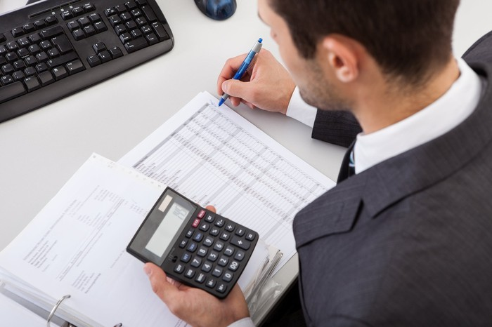 Man in suit using a calculator while reviewing a ledger.