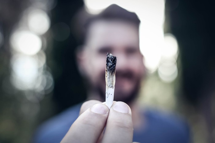 A man holding up a lit cannabis joint far in front of his face with his fingertips.