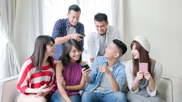 A group of young adults use their smartphones.