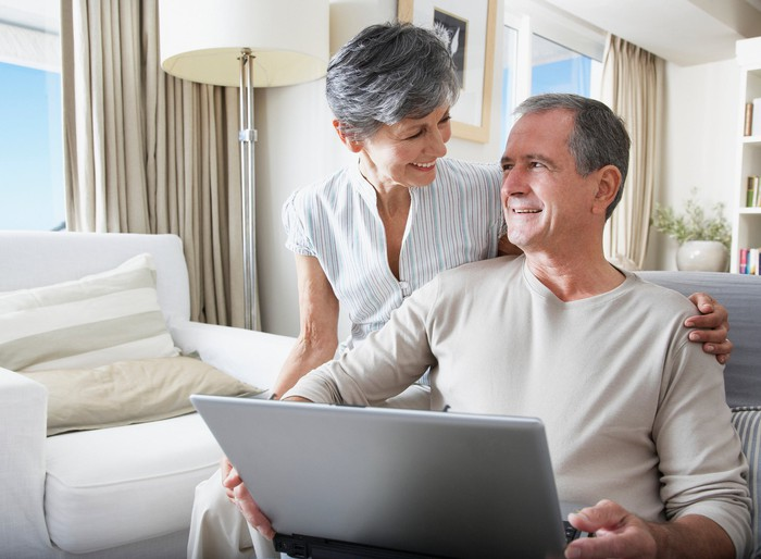 Woman sitting next to man with a laptop PC