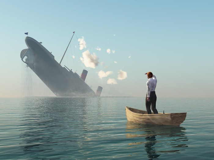 Man in lifeboat watching ship sinking