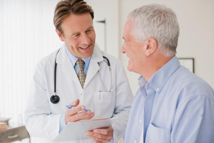 Male doctor speaking to elderly male patient