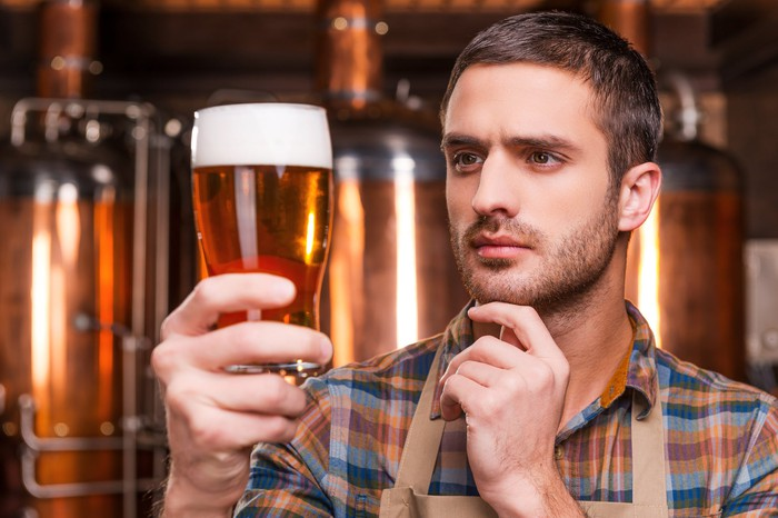 A brewer closely examining a pint of beer held in his right hand.