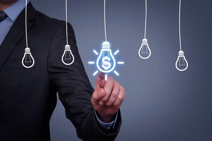 A man touching an idea bulb on a virtual screen.