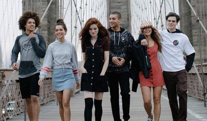 A group of young people walking on a bridge and wearing Tilly's clothing.