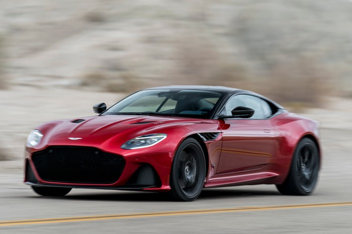 A red Aston Martin DBS Superleggera, a low-slung, front-engined high-performance coupe.