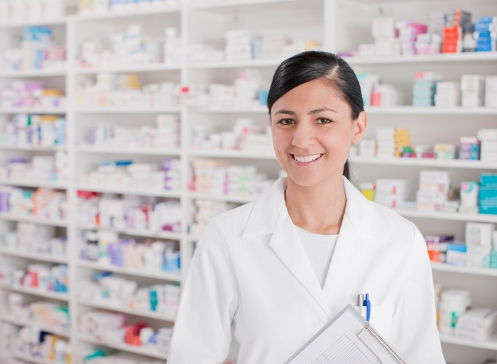 A pharmacist in a white lab coat is holding a clipboard and standing in front of shelves of prescription drugs.