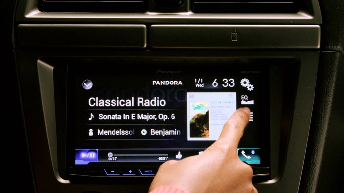 Pandora app playing through a car dashboard console.