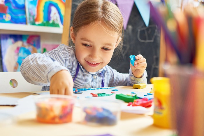 A smiling young girl hard at work with plasticine and other crafting supplies.