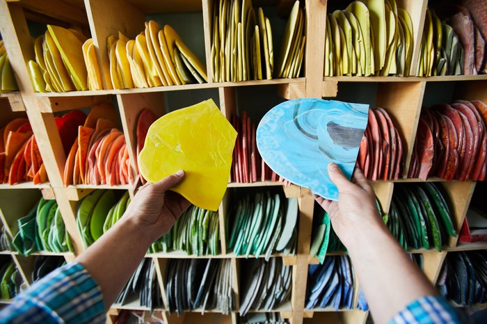 A person picking out colorful pieces of crafting material from a rack of shelves.