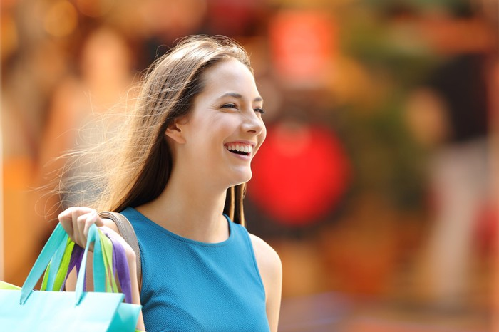 Smiling woman carrying shopping bags in the summer sun.