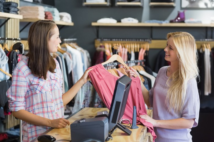 A smiling blonde woman purchasing a pink shirt from a young cashier.