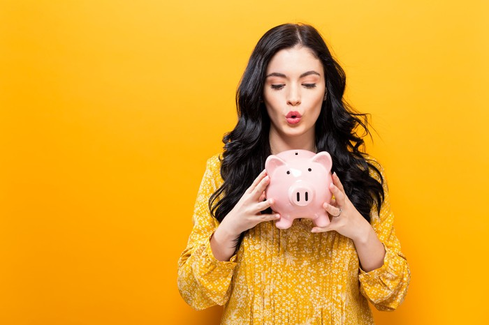 Woman looking down at piggy bank on yellow background.