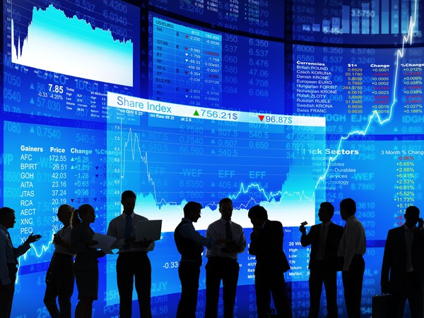 Numerous people in silhouette having a discussion with stock market tickers in the background