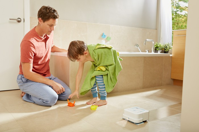 iRobot Braava jet robot cleaning a bathroom floor with a father and son in the background.