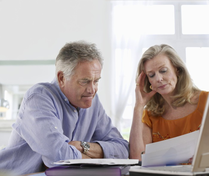 A visibly worried senior couple looking over paperwork while in front of their laptop.