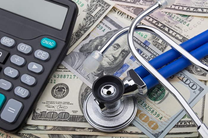 A calculator and a stethoscope on a pile of cash.