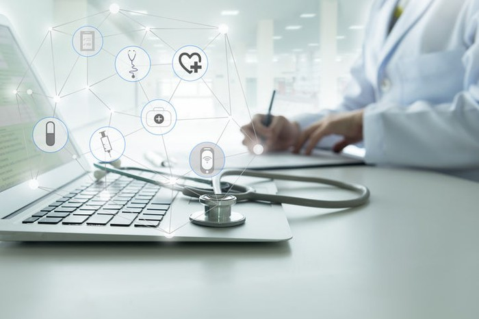 A doctor next to a laptop with various health icons floating over it.