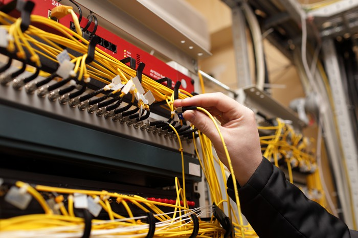 Technician pluggin in fiber-optic networking cables into a large switch or router.