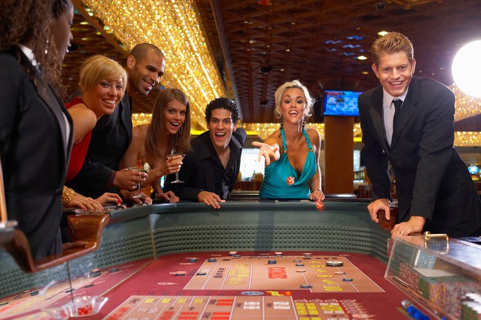 Well-dressed people smiling at a craps table with a woman throwing dice.