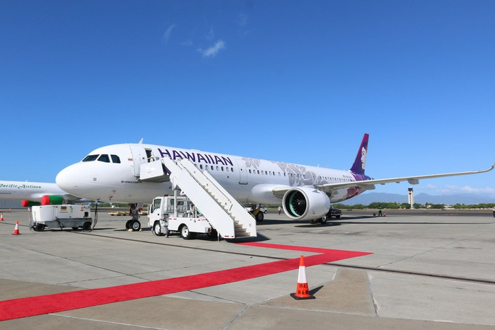 A red carpet sitting at the bottom of the stairs leading to a Hawaiian Airlines A321neo sitting on a tarmac under blue skies