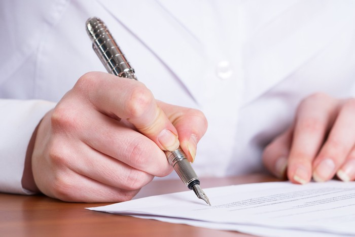 Man writing on document with pen