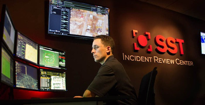 Employee in front of several monitoring screens at the company's Incident Review Center.