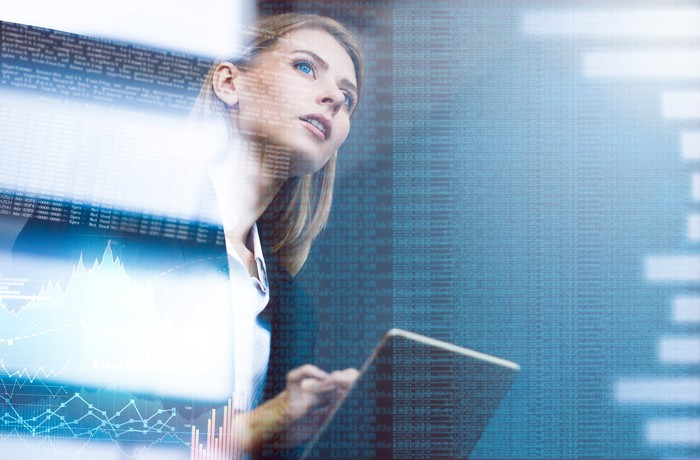 Woman holding laptop with superimposed lines of code; software programming concept.