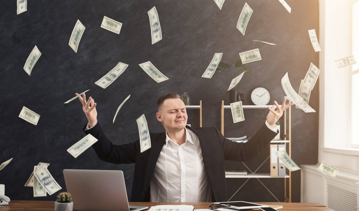 A content businessman throwing U.S. currency into the air while sitting at a desk.