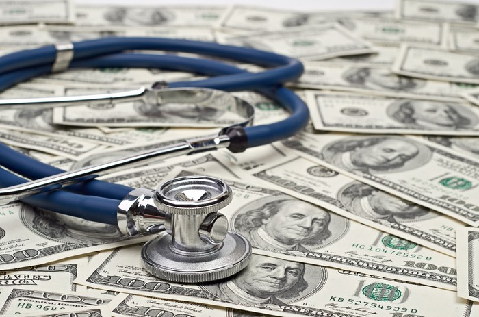A stethoscope sitting on a bed of $100 bills