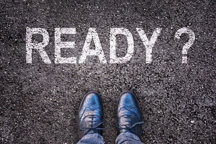 The word ready with a question mark printed on asphalt, with two feet in shoes showing, facing the word
