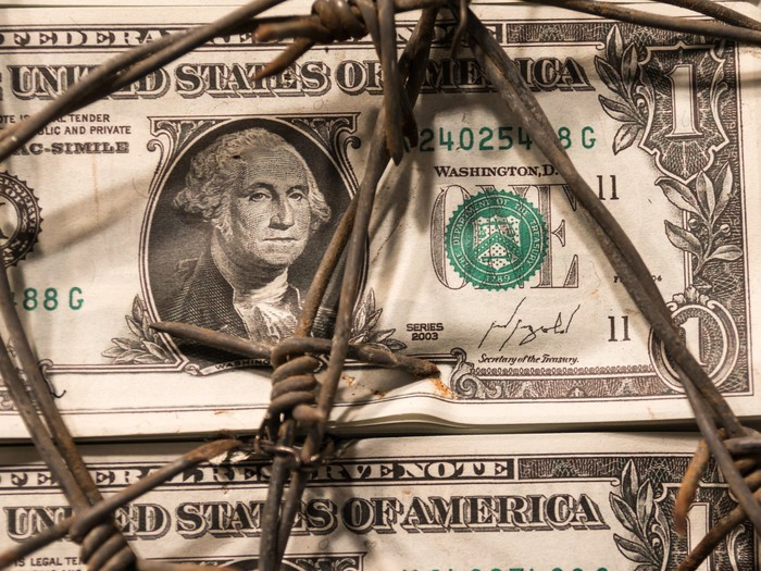 A U.S. $1 bill wrapped in barbed wire.