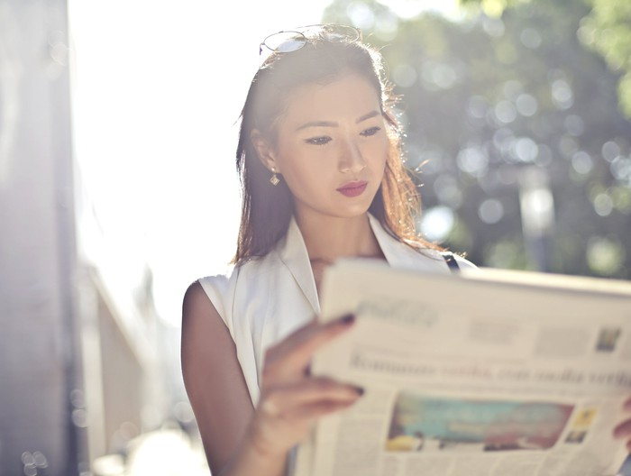 A young woman reads a newspaper.