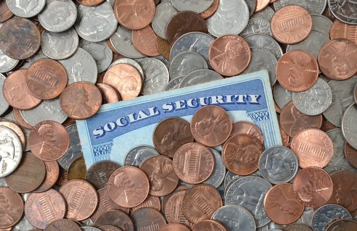 Social Security card embedded in a spread-out pile of coins.
