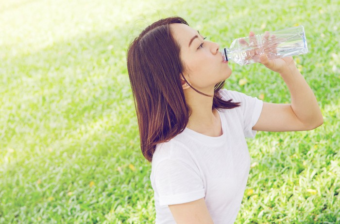 Woman drinking bottle of sparkling water