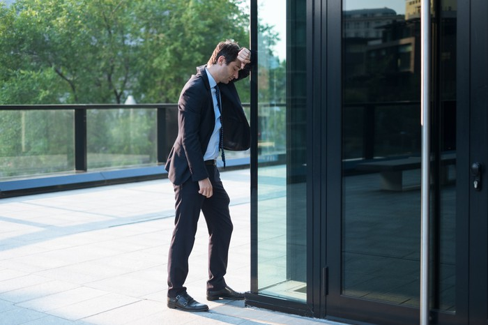 A businessman in a suit rests his head sullenly against a glass wall.