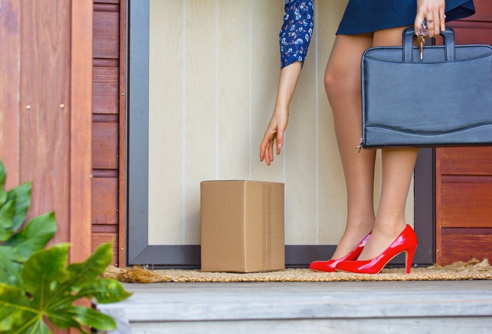 Woman holding briefcase bending down to pick up package at doorstep