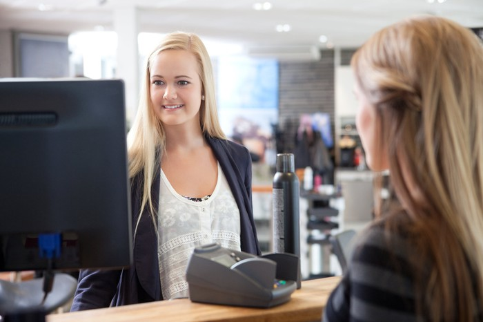 A cashier rings up hair products for a customer.