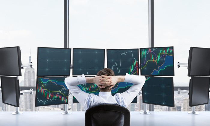 A man sitting with his fingers interlaced behind his head watching a bank of monitors showing graph lines.
