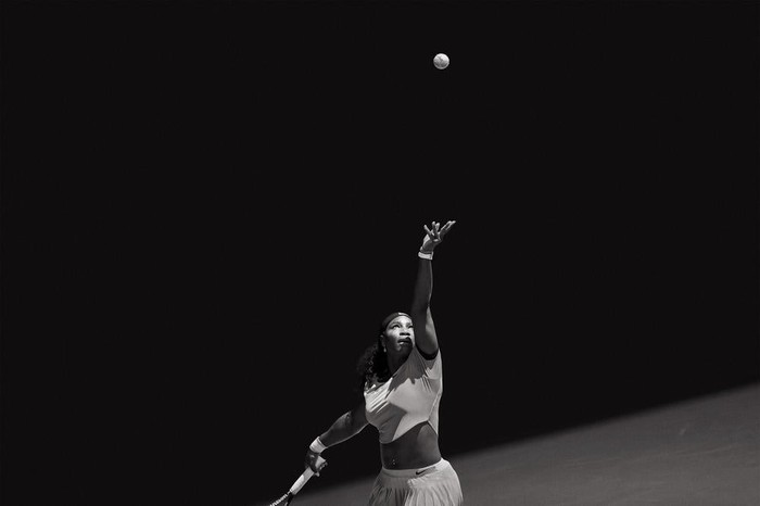 Serena Williams tossing a ball as she prepares for a serve.
