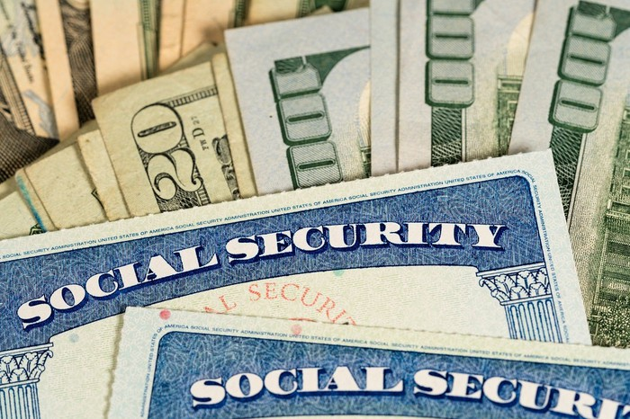 Social Security cards on top of $20 and $100 bills.