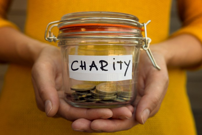 A person holds a jar with coins in it  that says charity