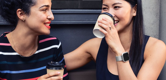 Two smiling women, drinking beverages. One woman is wearing a Fitbit Versa.