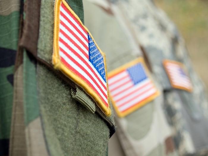 Shoulders of several people wearing military uniforms.