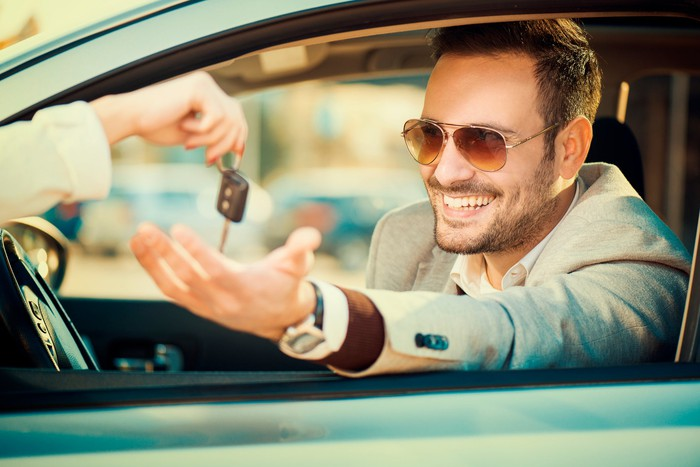 A smiling man is handed keys to a car as he sits in the driver's seat.